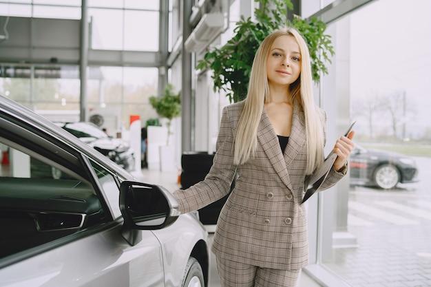 Señora en un salón de autos. mujer comprando el coche. mujer elegante con un traje marrón.