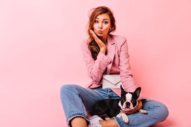 Señora sensual de jengibre sentada en el suelo con lindo bulldog francés. mujer de moda jocund posando con cachorro en pastel.