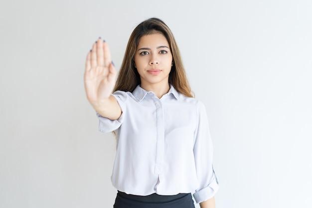 Señora seria mostrando palma abierta o gesto de parada