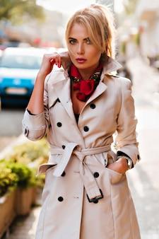 Señora seria en traje elegante de otoño posando en la calle con coche azul en el fondo