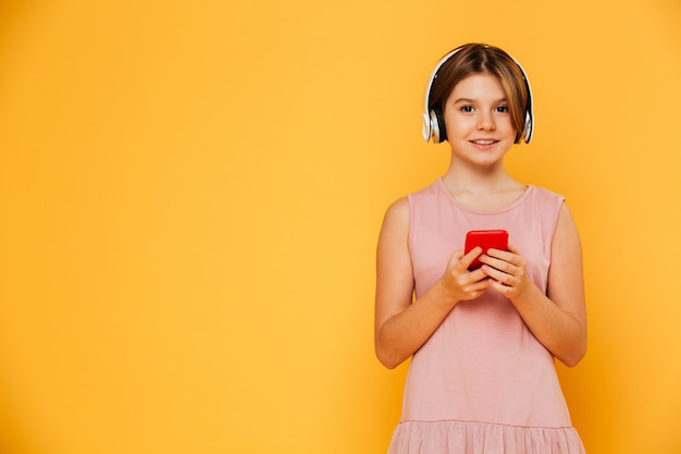 Señora sonriente con auriculares y smartphoe mirando cámara aislada