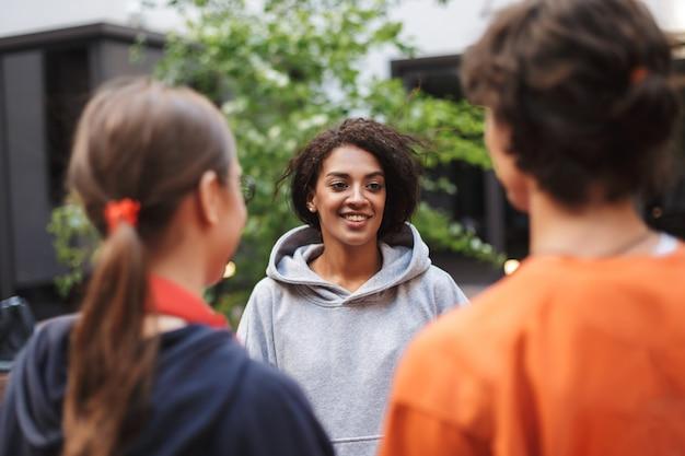 Señora sonriente con cabello rizado oscuro de pie y hablando felizmente con estudiantes en el patio de la universidad