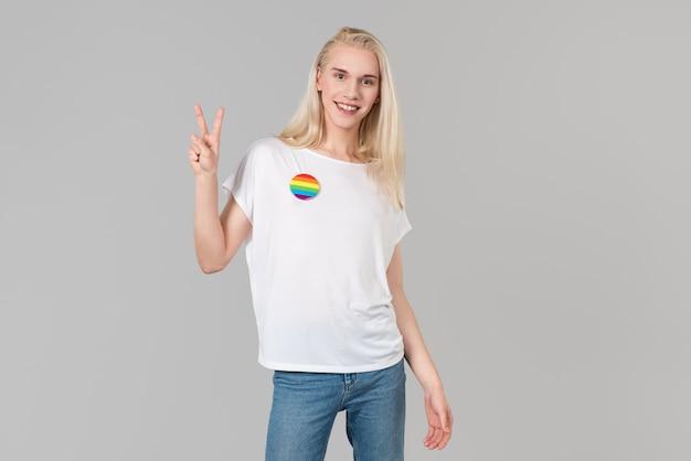 Señora sonriente con camiseta blanca y símbolo de la victoria