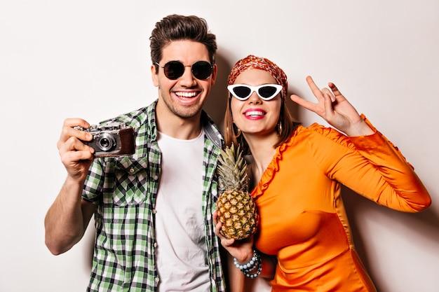 Señora sonriente con lápiz labial rojo vestida con vestido naranja muestra el signo de la paz y sostiene piña. chico con gafas de sol está sonriendo y haciendo fotos en cámara retro.
