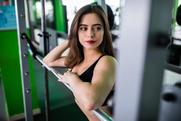 Señora sonriente se prepara para hacer ejercicio con barra en sportclub