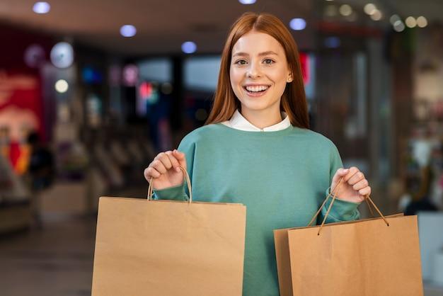 Señora sonriente que sostiene bolsos de compras