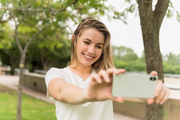 Señora sonriente que toma el selfie en el teléfono móvil en parque