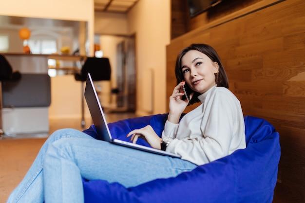 Señora sonriente que usa el teléfono móvil y la computadora portátil en la silla del bolso en oficina creativa