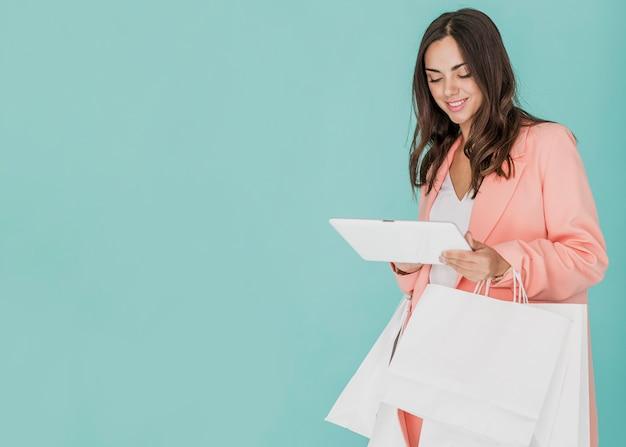 Señora sonriente con redes de compras mirando tablet