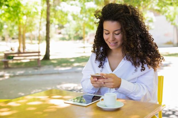 Señora sonriente con smartphone en la mesa de café en el parque