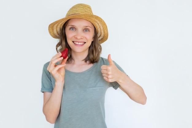 Señora sonriente en sombrero sosteniendo fresa madura con el pulgar hacia arriba