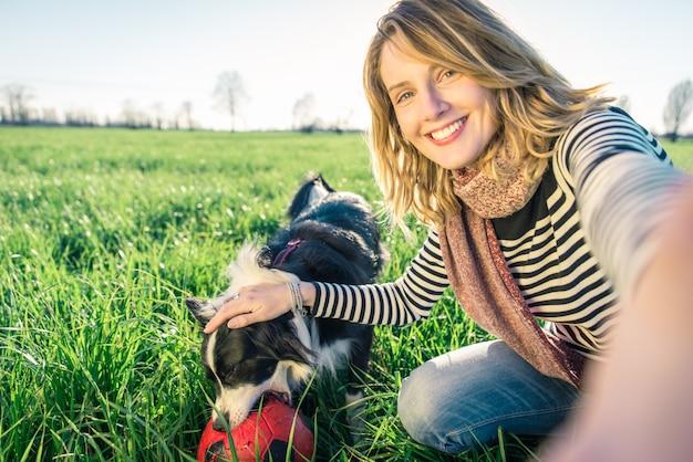 Señora sonriente tomando tiempo libre con su perro