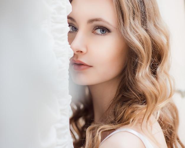 La señora de stuning con el pelo rubio oscuro y los ojos azules profundos brilla adentro