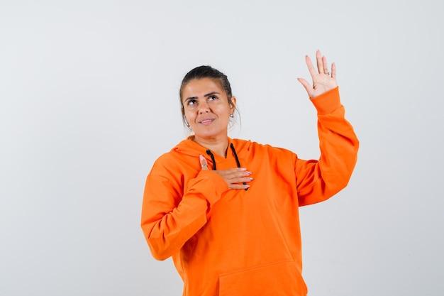 Señora en sudadera con capucha naranja agitando la mano para saludar y mirar alegre