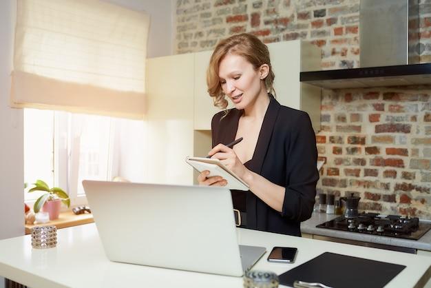 Una señora trabaja remotamente en una computadora portátil en una cocina. una niña con una sonrisa haciendo notas en el cuaderno durante el informe de un colega en una video conferencia en casa.