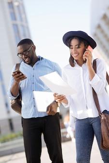 Señora trabajadora saliente segura que se acerca a clientes potenciales llamándolos mientras su colega escribe correos electrónicos