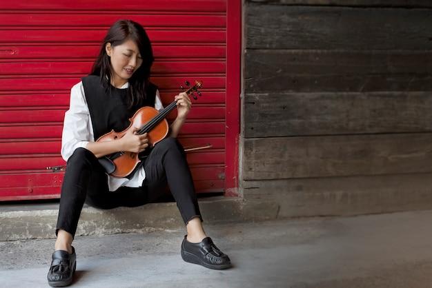 La señora usa el dedo para tocar las cuerdas de violín, la técnica de pizzicato