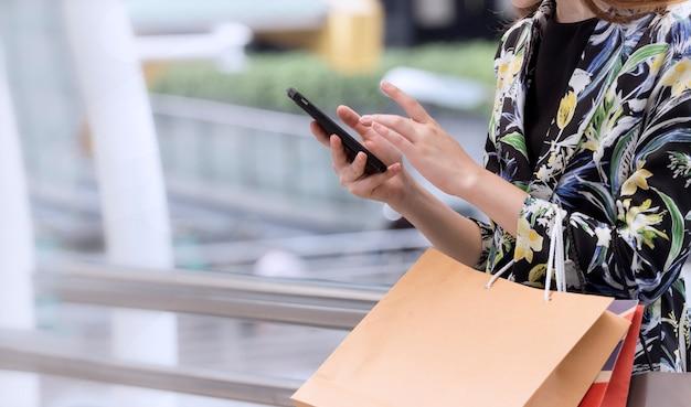 Señora usa el teléfono móvil y sostiene la bolsa de compras en sus manos
