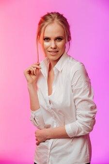 Señora vestida con camisa blanca posando sobre pared rosa.