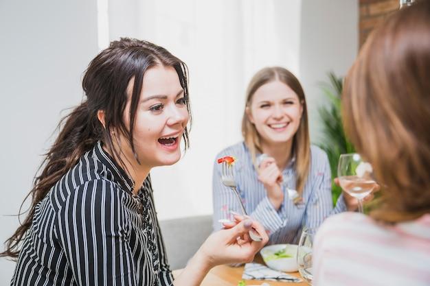 Señoras bebiendo y comiendo juntas en casa