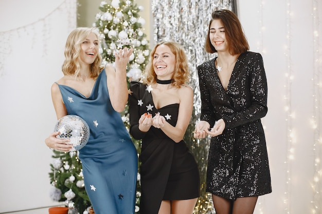 Señoras elegantes cerca del árbol de navidad. mujeres con ropa elegante.