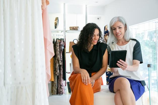 Señoras felices sentadas juntas y usando tableta, discutiendo ropa y compras en la tienda de moda. vista frontal. consumismo o concepto de compras
