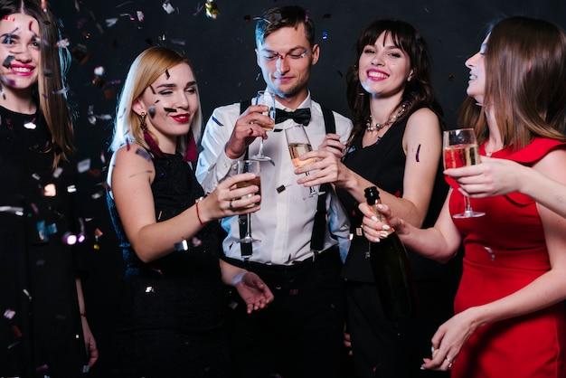 Señoras y hombres sonrientes en ropa de noche con vasos de bebidas entre tirar confeti