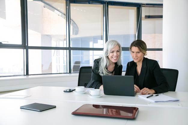 Señoras de negocios alegres mirando la pantalla del portátil, hablando y sonriendo mientras está sentado a la mesa con tazas de café en la oficina. concepto de comunicación y trabajo en equipo
