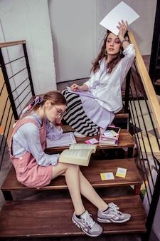 Señoras ocupadas. chicas ocupadas cansadas inspeccionando materiales y papeles en el espacio de trabajo conjunto y apoyándose en la barandilla de metal