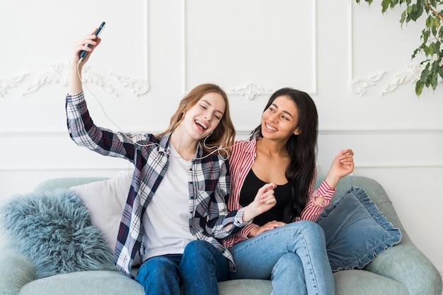 Señoras sentadas y escuchando música desde el teléfono.