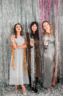 Señoras sonrientes jovenes que sostienen los vidrios entre la malla