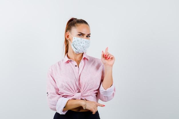 Señorita apuntando hacia arriba y hacia la derecha en camisa, máscara y mirando pensativa. vista frontal.