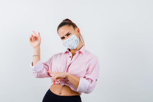 Señorita apuntando hacia arriba y hacia la izquierda en camisa, máscara y mirando pensativo, vista frontal.