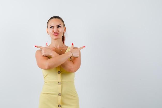 Señorita apuntando a derecha e izquierda con vestido amarillo y mirando pensativa. vista frontal.