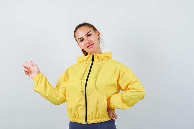 Señorita apuntando a un lado en chaqueta amarilla y mirando confiado, vista frontal.