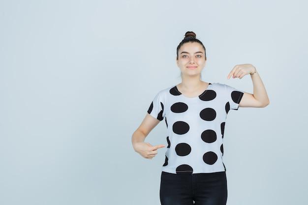 Señorita apuntando a sí misma en camiseta, jeans y luciendo orgullosa, vista frontal.