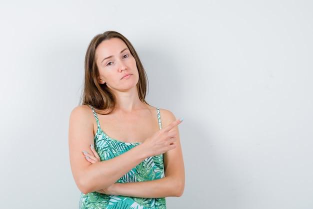 Señorita en blusa apuntando a la esquina superior derecha y mirando confiada, vista frontal.