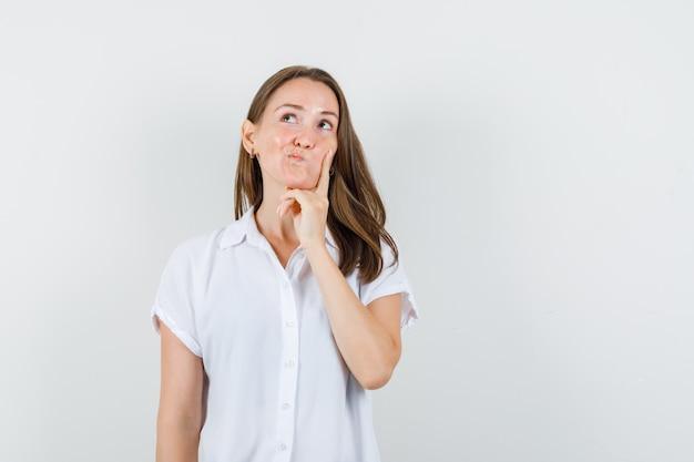 Señorita en blusa blanca sosteniendo la mano en la mejilla y mirando pensativa