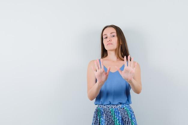 Señorita en blusa, falda rechazando algo y mirando segura, vista frontal.