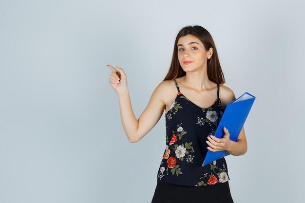 Señorita en blusa, falda sosteniendo carpeta, apuntando a un lado y mirando alegre, vista frontal.