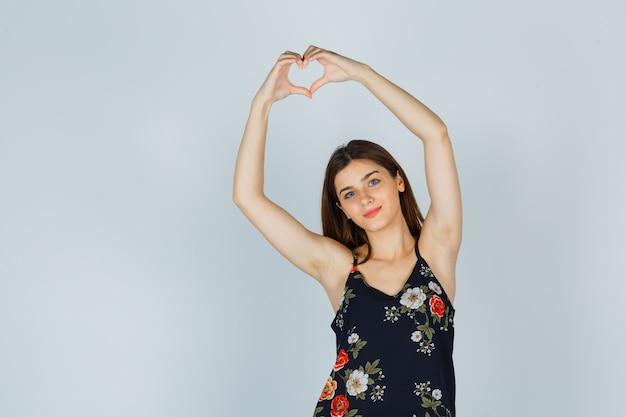 Señorita en blusa mostrando gesto de corazón y mirando alegre, vista frontal.