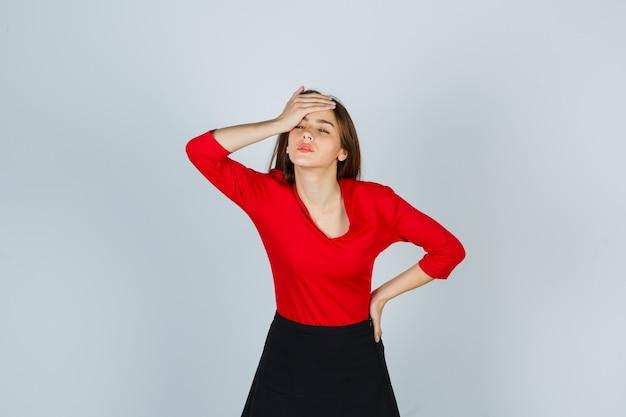 Señorita en blusa roja, falda sosteniendo la mano en la frente mientras mantiene la mano