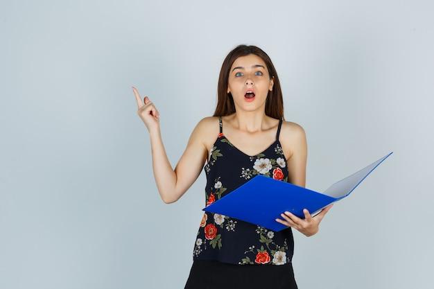 Señorita en blusa sosteniendo la carpeta abierta, apuntando hacia arriba y mirando sorprendido, vista frontal.
