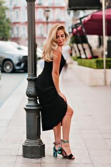 Señorita bronceada en zapatos de tacón posando juguetonamente junto a la farola y mirando hacia abajo