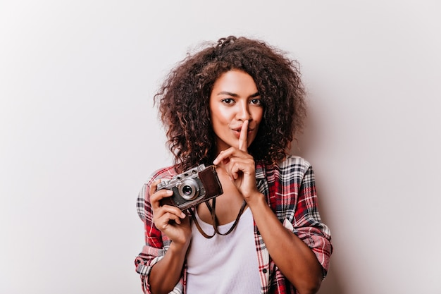 Señorita de buen humor con cámara de pie con una sonrisa. chica negra refinada tomando fotografías.