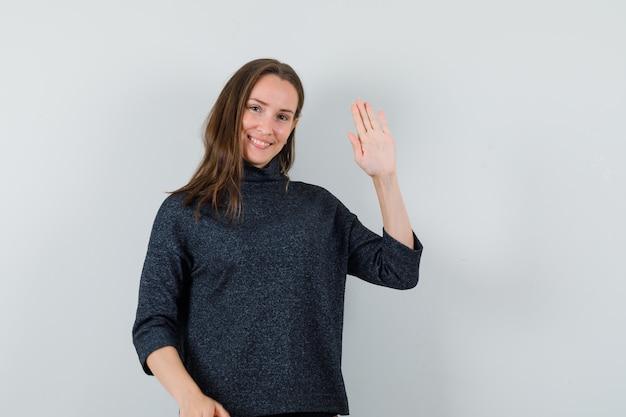 Señorita en camisa agitando la mano para saludar y mirar alegre