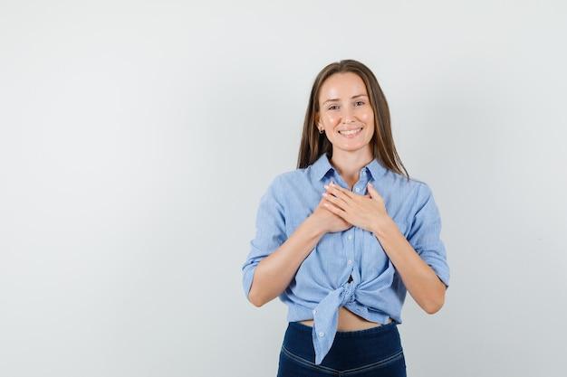 Señorita en camisa azul, pantalones tomados de la mano en el pecho y mirando agradecido