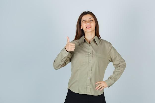 Señorita en camisa, falda mostrando el pulgar hacia arriba mientras guiña un ojo y se ve feliz, vista frontal.