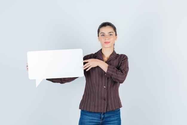 Señorita en camisa, jeans mostrando carteles de papel y mirando confiada, vista frontal.