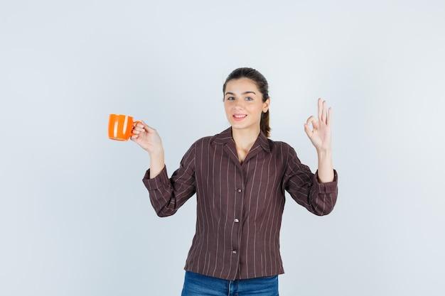 Señorita en camisa, jeans mostrando gesto ok, manteniendo la taza y mirando feliz, vista frontal.